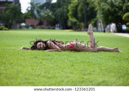 Beautiful young woman in pink bikini with long brown hair on the lawn - stock photo