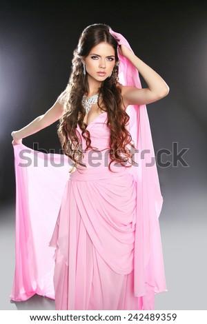 Beautiful young woman in pink chiffon dress. Makeup. Long wavy hair styling. Studio photo. - stock photo