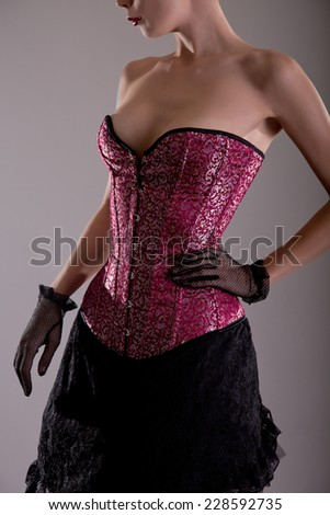 Beautiful young woman in pink corset with floral pattern, studio shot  - stock photo