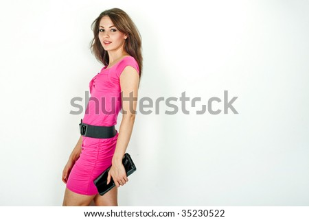 Beautiful young woman in pink dress smiling on white background - stock photo