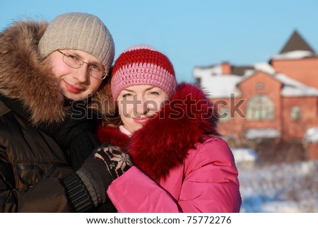 beautiful young woman in pink jacket and man in glasses at winter outdoors, house - stock photo
