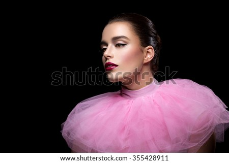 Beautiful young woman in pink lace fluffy collar over black background. Copy space. - stock photo