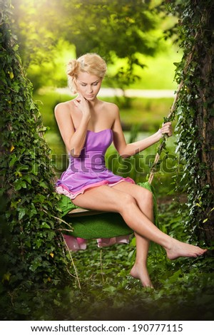 Beautiful young woman in pink short dress dreaming in a leaves decorated swing between two trees. Gorgeous fair hair girl posing in garden, outdoor shot. Attractive blonde swinging on leafy swing - stock photo