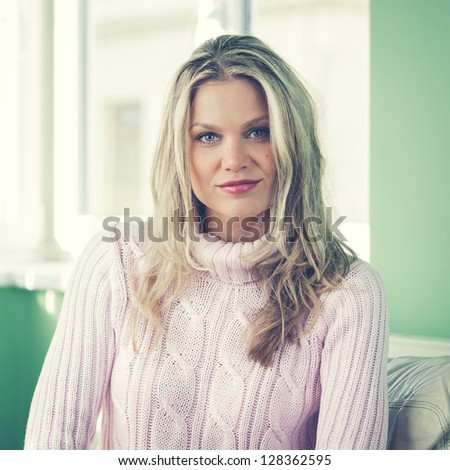 Beautiful Young Woman in Pink Sweater Posing By the Window in the Living Room (vintage style, color toned image) - stock photo