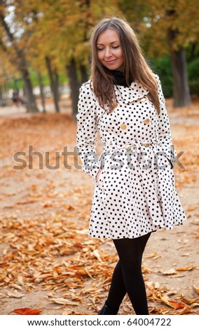 Beautiful young woman in polka dot trench at fall - stock photo