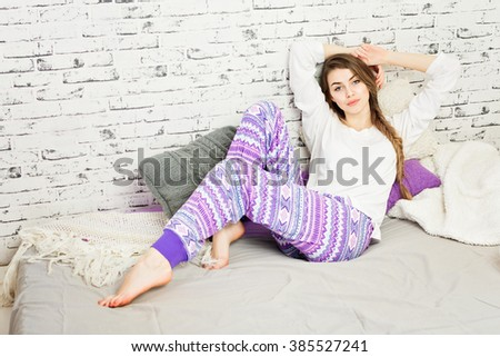 Beautiful young woman in purple and white pajamas lying on bed with arms above her head, posing. Modern teenage girl with braided hair in her modern bedroom relaxing. Horizontal, retouched. - stock photo