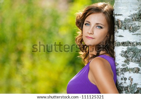 Beautiful young woman in purple dress is based on sad birch, against green of summer park. - stock photo