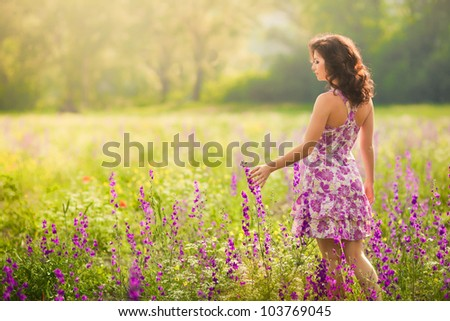 Beautiful young woman in purple flowers outdoors - stock photo