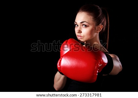 Beautiful young woman in red boxing gloves over black background - stock photo