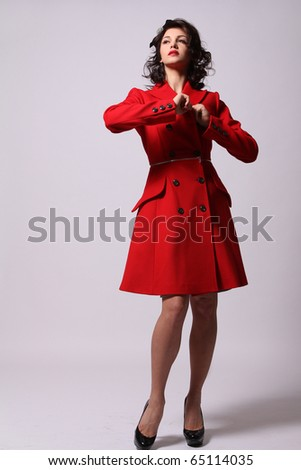 Beautiful young woman in red coat posing on white background
