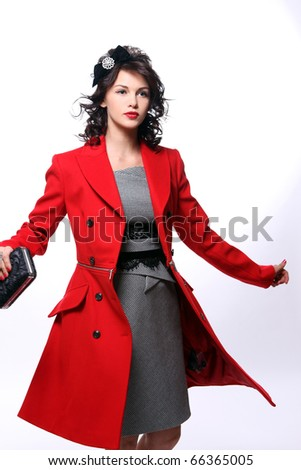 Beautiful young woman in red coat posing on white background - stock photo