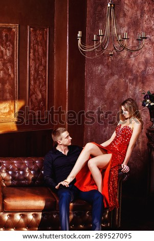 Beautiful young woman in red dress is flirting with elegant husband in bedroom. - stock photo