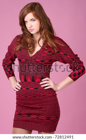 Beautiful young woman in red dress over red background - stock photo
