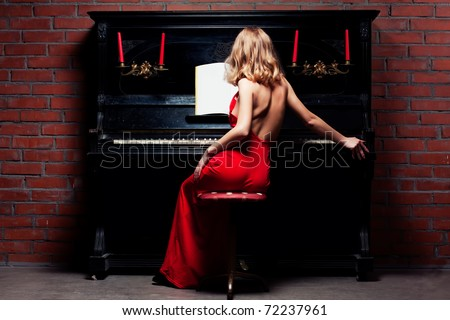 beautiful young woman in red dress playing the piano - stock photo