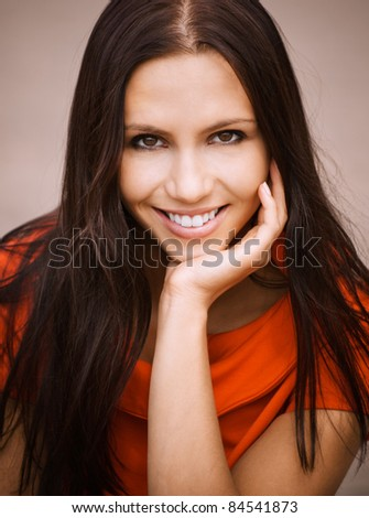 Beautiful young woman in red dress props up hand chin and laughs. - stock photo