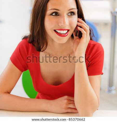 Beautiful young woman in red dress sits at little table in cafe and order expects. - stock photo
