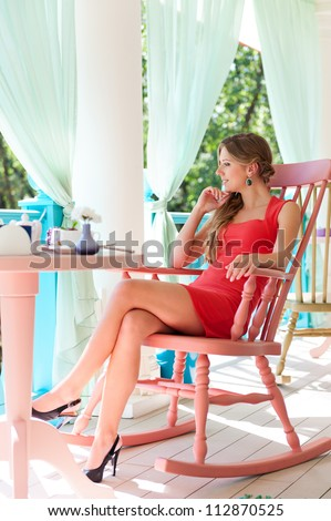beautiful young woman in red dress sitting at light cafe - stock photo
