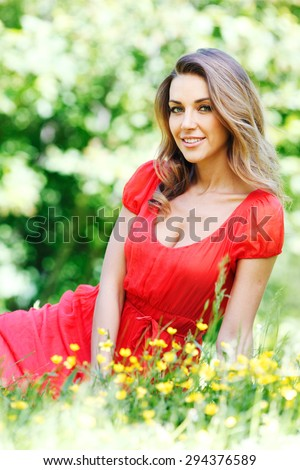 beautiful young woman in red dress sitting on grass - stock photo
