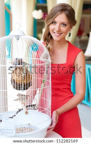 beautiful young woman in red dress standing near white cage with birds - stock photo