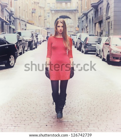 beautiful young woman in red dress walking on the modern city street near with cars