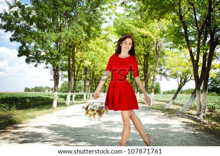 Beautiful young woman in red  dress with wild flowers in the basket