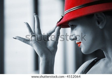Beautiful young woman in red hat posing. Shallow DOF. - stock photo