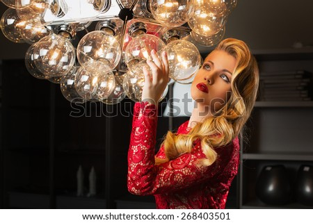 Beautiful young woman in red lace gown standing near big lamp with many bowls - stock photo