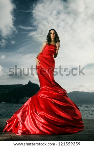 beautiful young woman in red long dress near the sea - stock photo