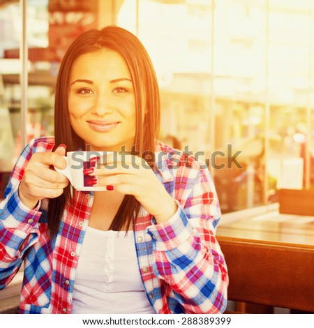 Beautiful young woman in red plaid shirt smiling holding a cup of coffee sitting in cafe bar outdoors on sunny summer day. Retouched, vibrant colors, square format.