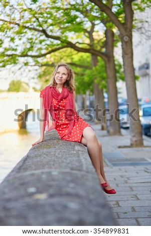 Beautiful young woman in red polka dot dress near the Seine on a nice summer day