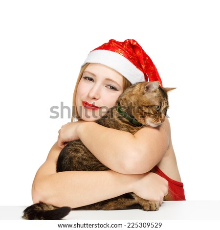 Beautiful young woman in red santa cap embracing tabby cat in collar isolated on white background. Shallow DOF, focus on cat eyes. - stock photo