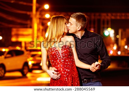 Beautiful young woman in red sparkling dress is passionately kissing elegant macho man at city street at bright lights and moving cars blurred background.