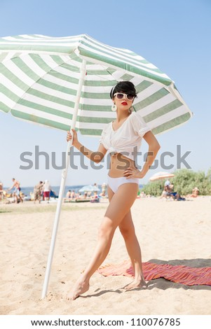 beautiful young woman in retro style by color umbrella on the beach. outdoors - stock photo