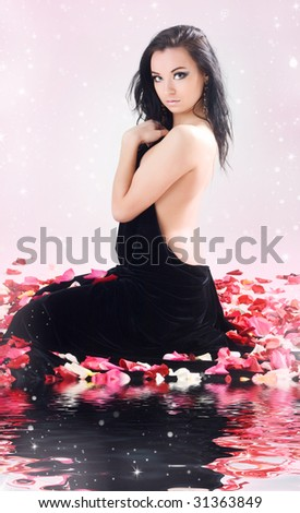 Beautiful young woman in rose petals - stock photo