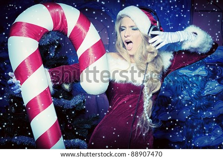 Beautiful young woman in Santa Claus clothes and headphones over Christmas background. - stock photo