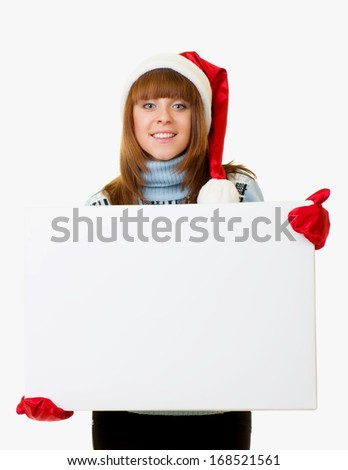 Beautiful young woman in Santa Claus clothes leaning on blank board on white background. - stock photo