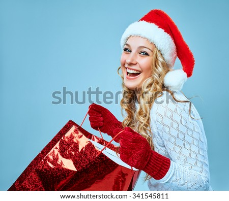 Beautiful young woman in Santa Claus clothes with a gift on a blue background - stock photo
