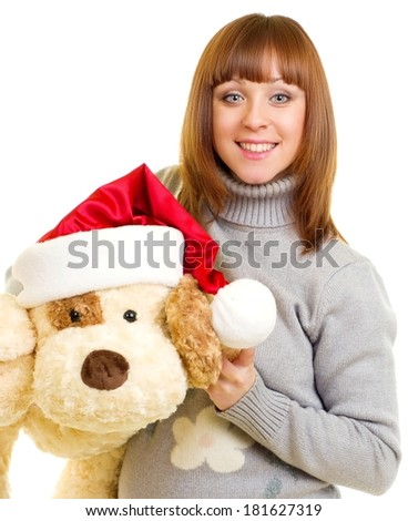 Beautiful young woman in Santa Claus clothes with toy dog - stock photo