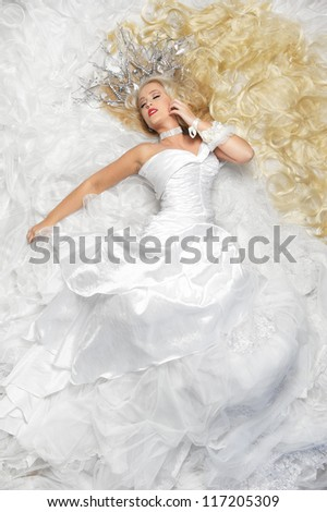 Beautiful young woman in sensual pose on a bed of white lace fabric - stock photo