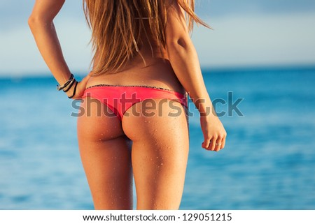 beautiful young woman in sexy bikini at the beach at sunset in Hawaii - stock photo