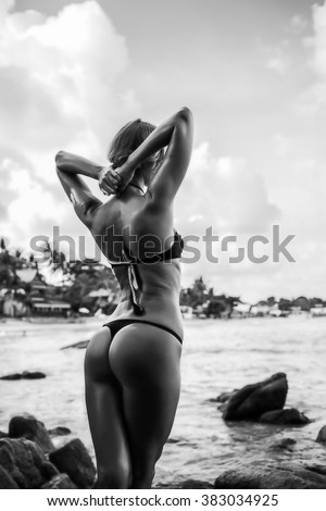 beautiful young woman in sexy bikini at the beach at sunset in Thailand. Black and white. - stock photo