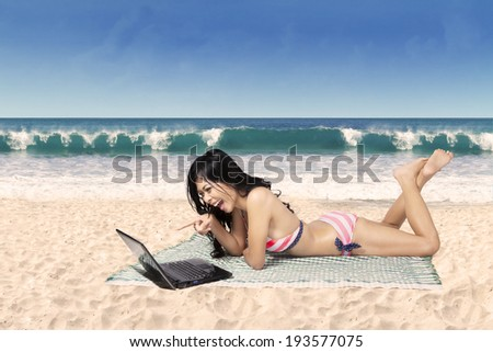 Beautiful young woman in sexy bikini working with laptop on the tropical beach