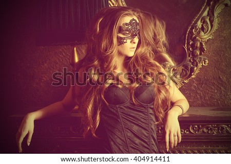 Beautiful young woman in sexy lingerie and black mask alluring in vintage apartment.  - stock photo