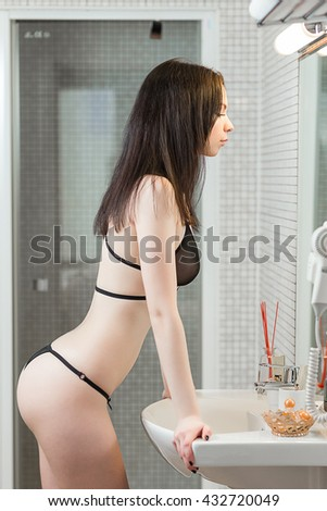 Beautiful young woman in sexy lingerie looking in the mirror in the bathroom in apartments. - stock photo