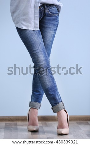 Beautiful young woman in shirt and jeans on blue wall background