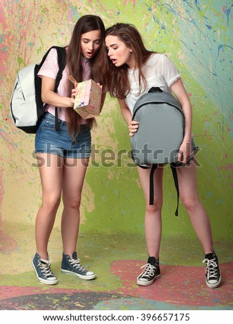 Beautiful young woman in shorts and with backpacks looking at a box - stock photo