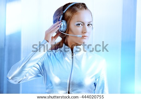 Beautiful young woman in silver latex costume with futuristic hairstyle and make-up. Sci-fi style. - stock photo
