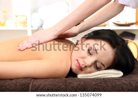 Beautiful young woman in spa salon getting massage, on bright background