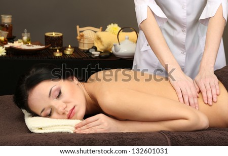 Beautiful young woman in spa salon getting massage, on dark background - stock photo