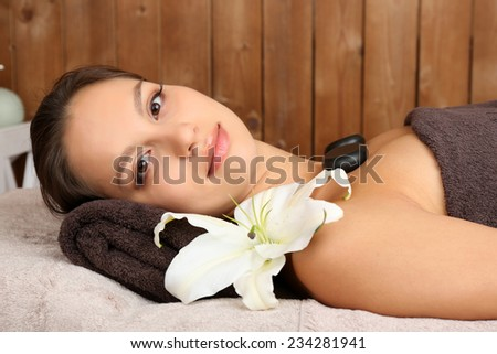 Beautiful young woman in spa salon with spa stones  - stock photo